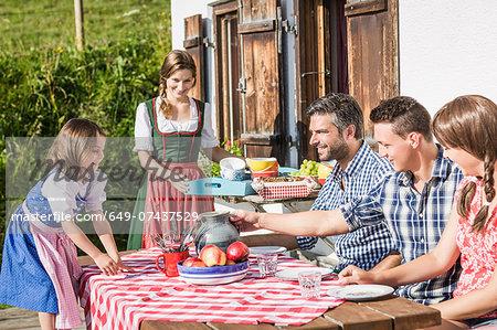 Friends enjoying breakfast outside chalet, Tyrol, Austria