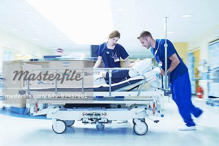 Two medics pushing gurney in hospital emergency room