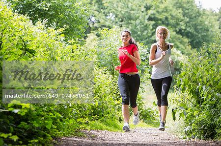 Women jogging through forest