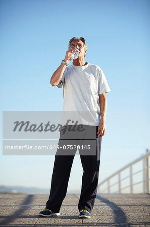 Senior man drinking water on walk
