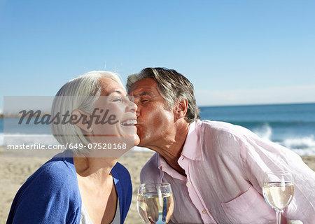 Man pecking woman on cheek