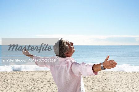 Senior man on beach with arms outspread
