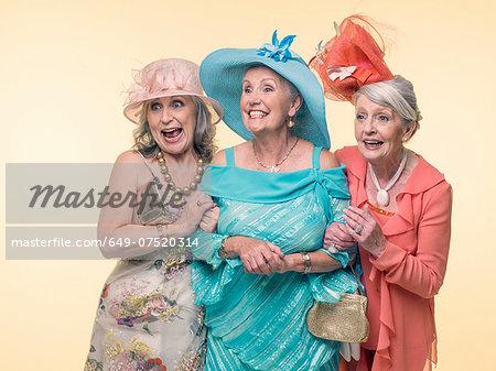 Studio portrait of three happy glamorous senior women