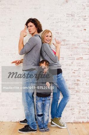 Studio portrait of couple and son making gun hand gestures