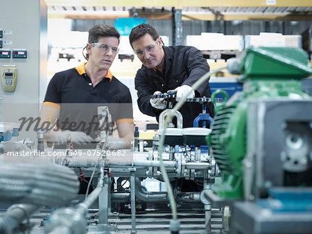 Engineers with industrial pump testing rig in factory