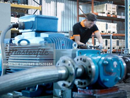 Engineer with industrial pump testing rig in factory