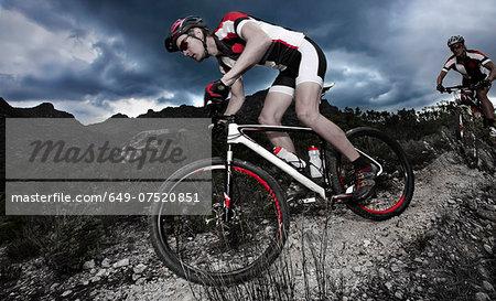 Young couple riding mountain bikes down mountain path