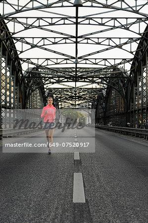 Young female runner across bridge