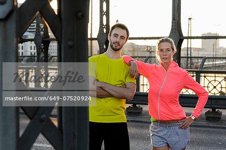 Portrait of young running couple on bridge