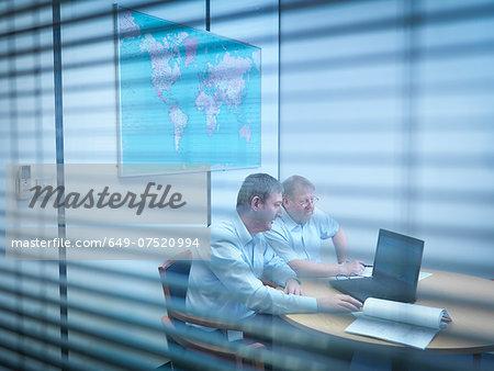 Engineers using laptop in meeting room