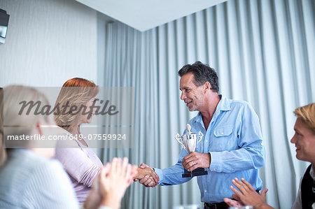 Mature businesswomen receiving trophy at meeting