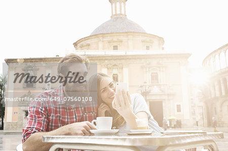 Young couple having coffee in sidewalk cafe, Plaza de la Virgen, Valencia, Spain