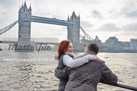 Mature tourist couple and Tower Bridge, London, UK