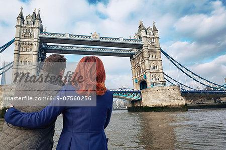 Mature tourist couple photographing Tower Bridge, London, UK