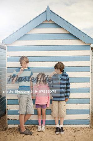 Three children eating ice cream cones, Southwold, Sussex, UK