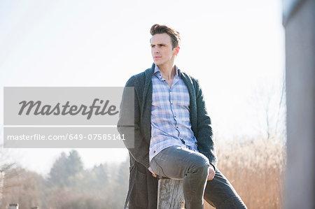 Mid adult man sitting on post on pier