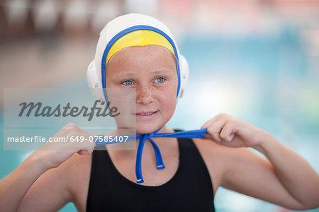 Portrait of schoolgirl water polo player fastening swimming cap