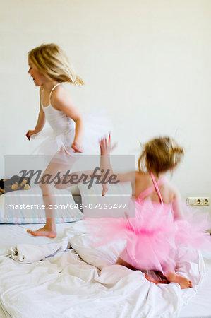 Sisters dressed as ballet dancers running on bed