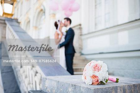 Mid adult bride and groom kissing on stairway