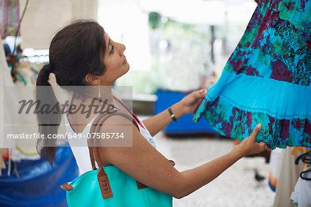 Mature woman looking at skirt on market stall, Ipanema, Rio De Janeiro, Brazil