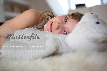 Girl lying on furry bed with teddy bear