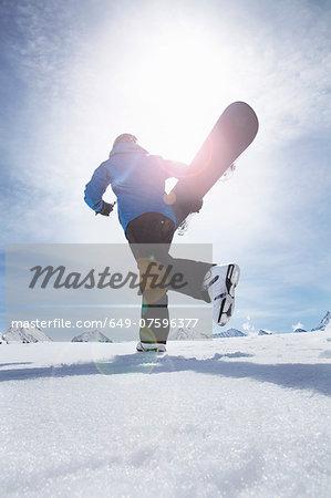 Mature man carrying his snowboard uphill, Obergurgl, Austria