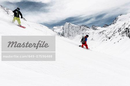 Two men snowboarding downhill, Obergurgl, Austria