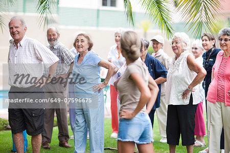 Large group of seniors exercising in retirement villa garden
