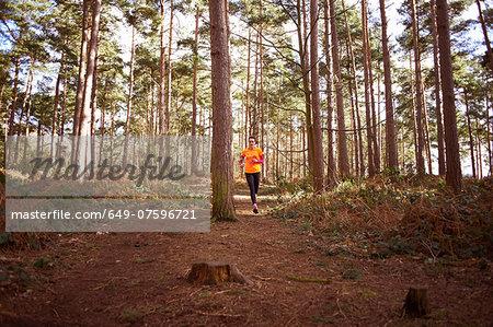 Mature woman running through a forest