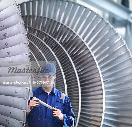 Engineer inspecting steam turbine blade in workshop