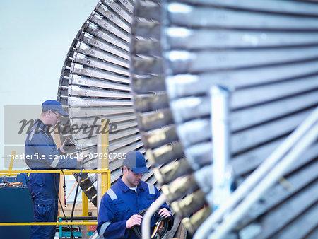 Engineers repairing steam turbine in repair bay in workshop