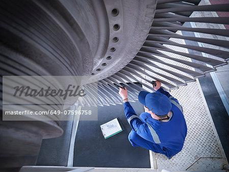 Engineer inspecting steam turbine in repair works