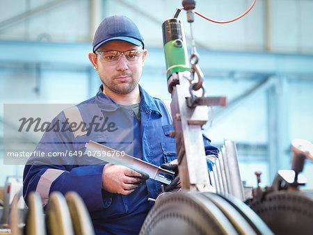 Portrait of engineer fitting blades to steam turbine in repair works