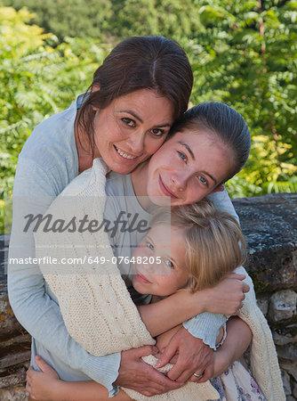 Mother and daughters in garden, hugging