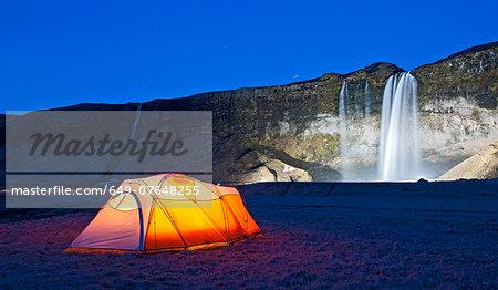 Illuminated tent and Seljalandsfoss waterfall at night, South Iceland