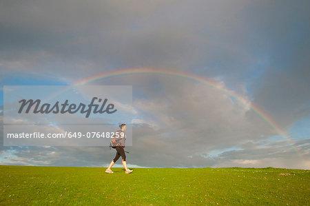 Young female hiker, hiking below rainbow