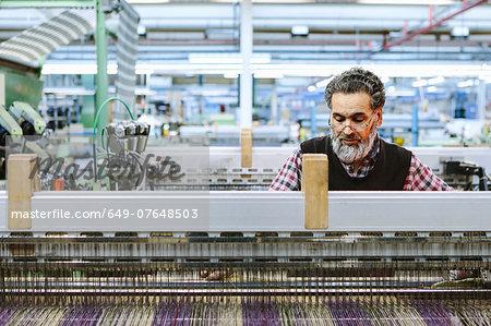 Male factory worker on weaving machine in woollen mill