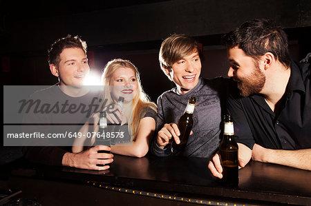 Four friends drinking bottled beer in nightclub