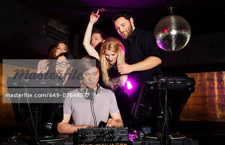 Group of friends watching DJ in nightclub