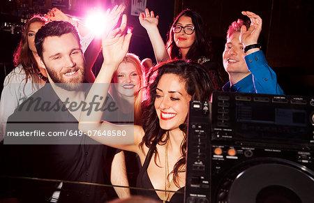 Group of young men and women dancing in nightclub
