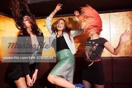 Four female friends dancing in nightclub