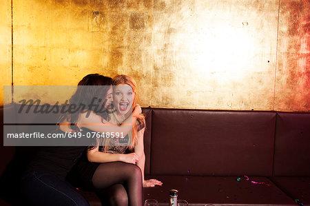 Two female friends having a laugh in nightclub