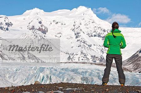 Rear view of mature female hiker in mountains, Svinafellsjokull, Vatnajokull National Park, Iceland