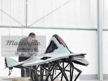 Automotive designer inspecting part-built supercar in car factory