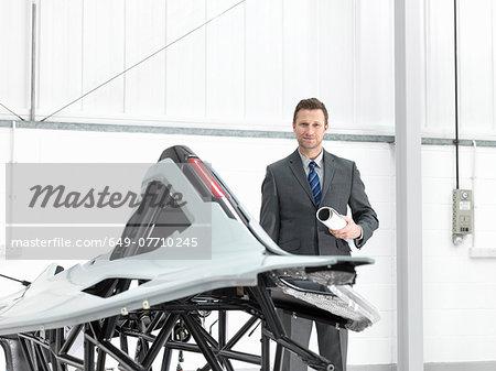 Automotive designer with part-built supercar in car factory, portrait