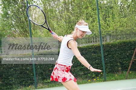 Mature woman playing tennis
