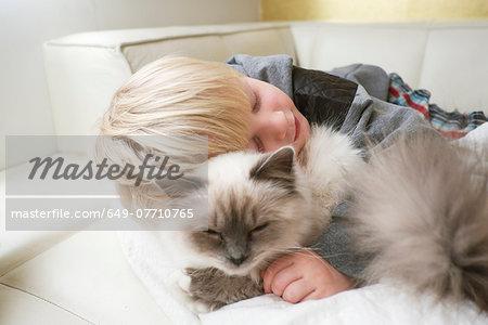 Cute three year old boy with eyes closed hugging cat on sofa