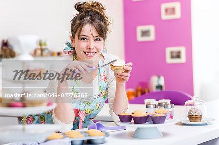 woman decorating cupcake stock photo