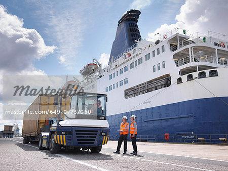 Port workers on dock side beside ship