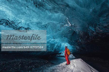 Man looking up in ice cave, Vatnajokull Glacier, Vatnajokull National Park, Iceland